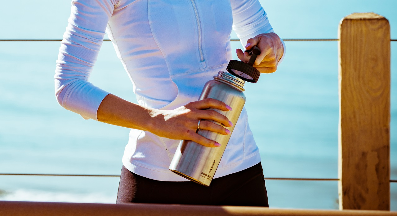 A woman takes the lid off a stainless steel water bottle she is holding.
