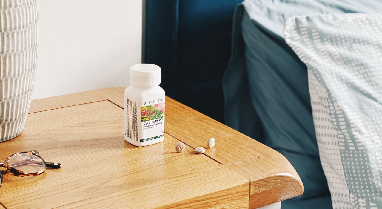 Three tablets lie next to a bottle of Nutrilite Sleep Health sitting on a nightstand. A pair of glasses are to the left of the frame and the bed can be seen to the right.