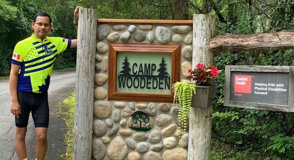 Amway IBO Ganesh Shenroy poses with sign for Camp Woodeden, an Easterseals camp for children with disabilities.