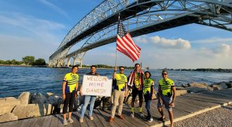 Amway IBO Ganesh Shenroy and his team of riders pose with a welcome sign upon reaching Michigan in Port Huron.