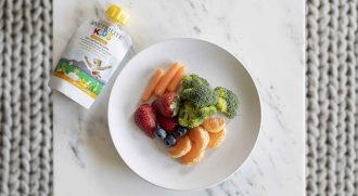 A Nutrilite Kids Smoothie lies next to a healthy colorful snack of fruits and vegetables on a plate seen from above.