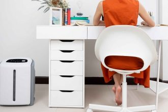 The Atmosphere Mini Air Treatment System sits next to a desk in a home office.